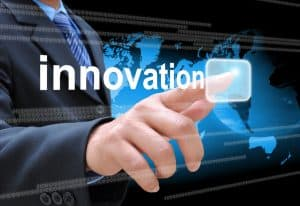 businessman hand pushing innovation button on a touch screen int